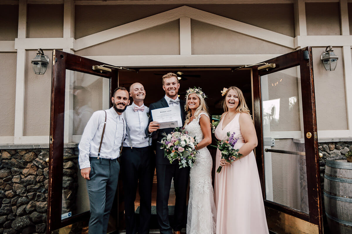 A photo of a group of happy people on a wedding day with open doors behind them