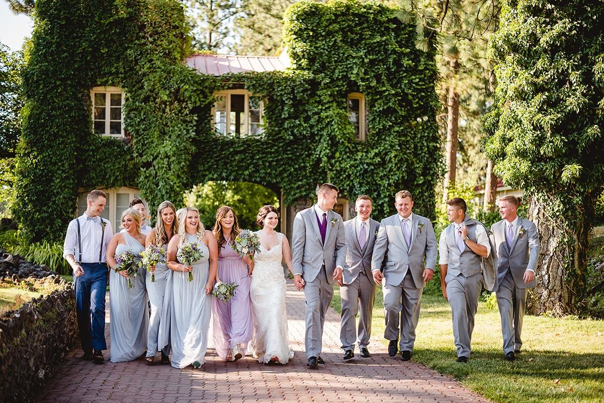 A photo of a wedding party in front of a lush overgrown gatehouse on the Estate grounds