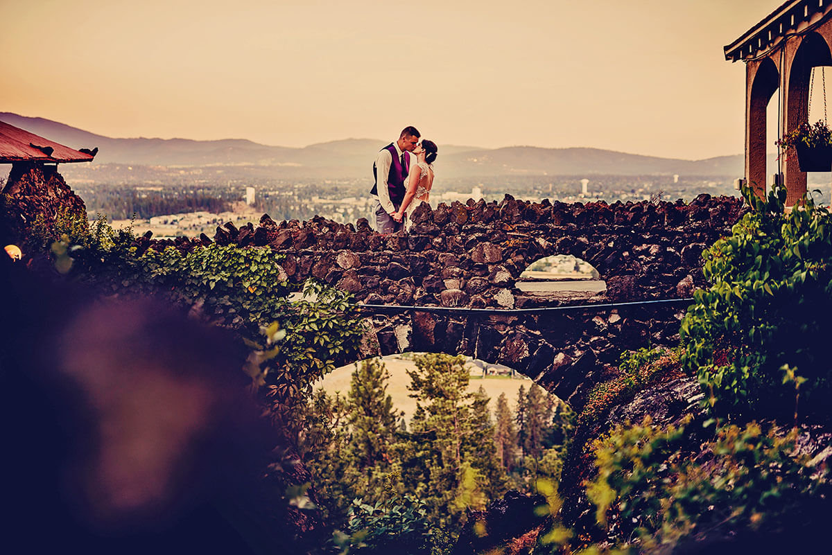 A photo of a bride and groom on the bridge connecting to the Cliff House Estate