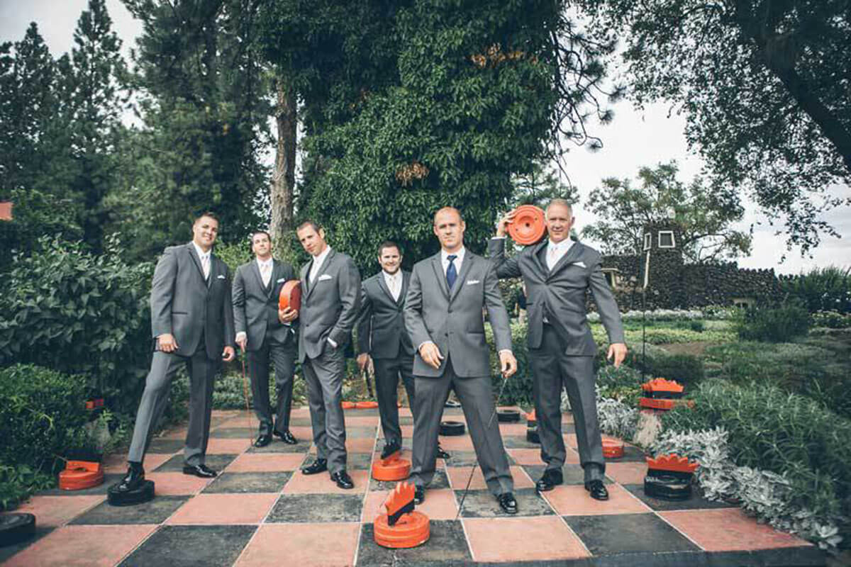 A photo of groomsmen on the life-size checkerboard