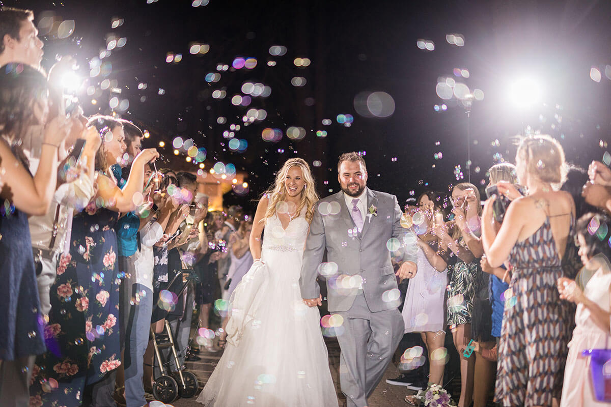 A photo of bride and groom surrounded by friends and family with lights and a dark sky