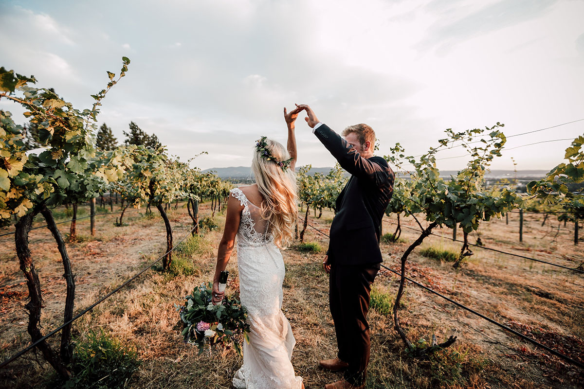 A photo of a bride and groom walking hand-in-hand through the vineyard
