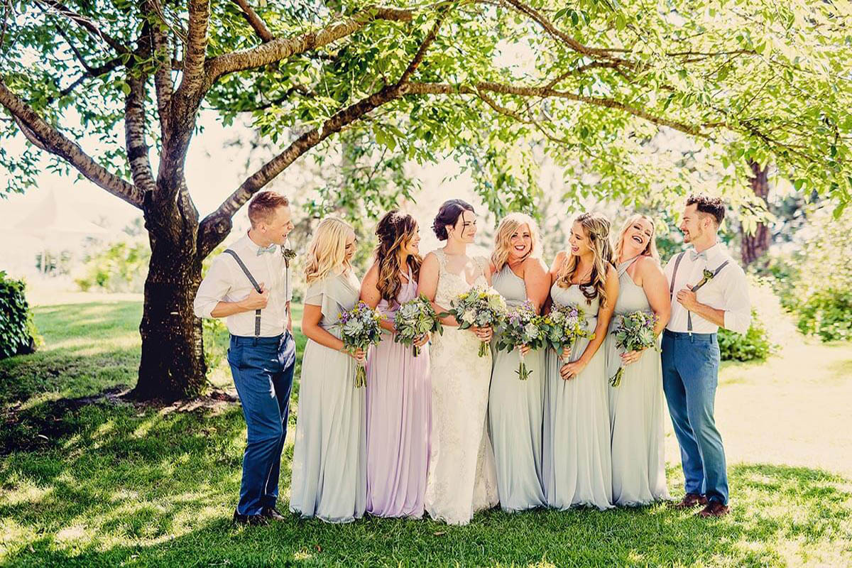 A photo of a wedding party beneath green trees