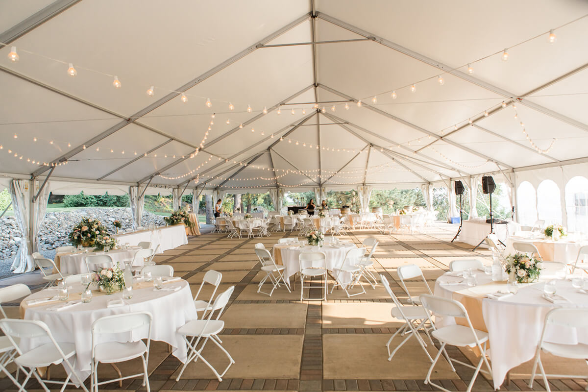 a photo of the wedding tent with lights strung to the ceiling and tables set out beneath