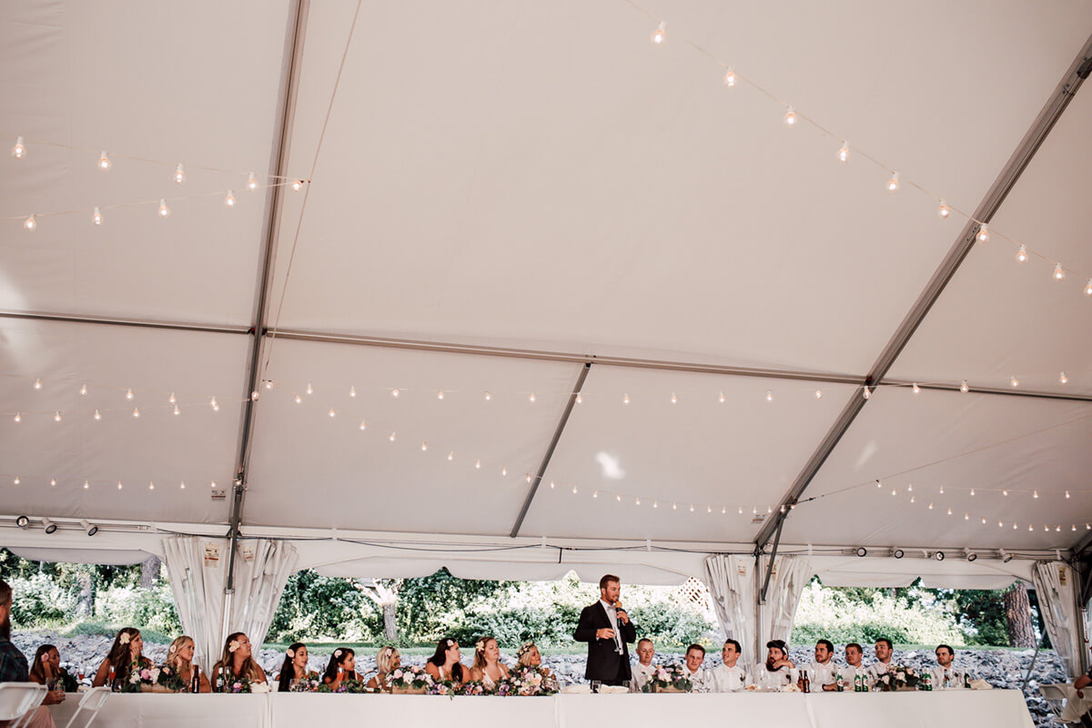 A photo of a man giving a speech at a wedding ceremony with lights hanging from the ceiling