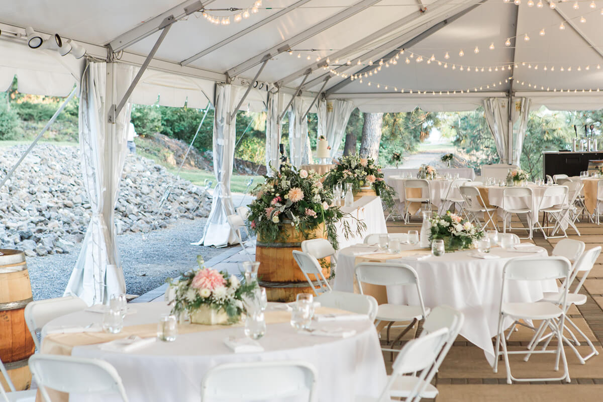 A photo of the interior of the wedding tent with flowers and set tables