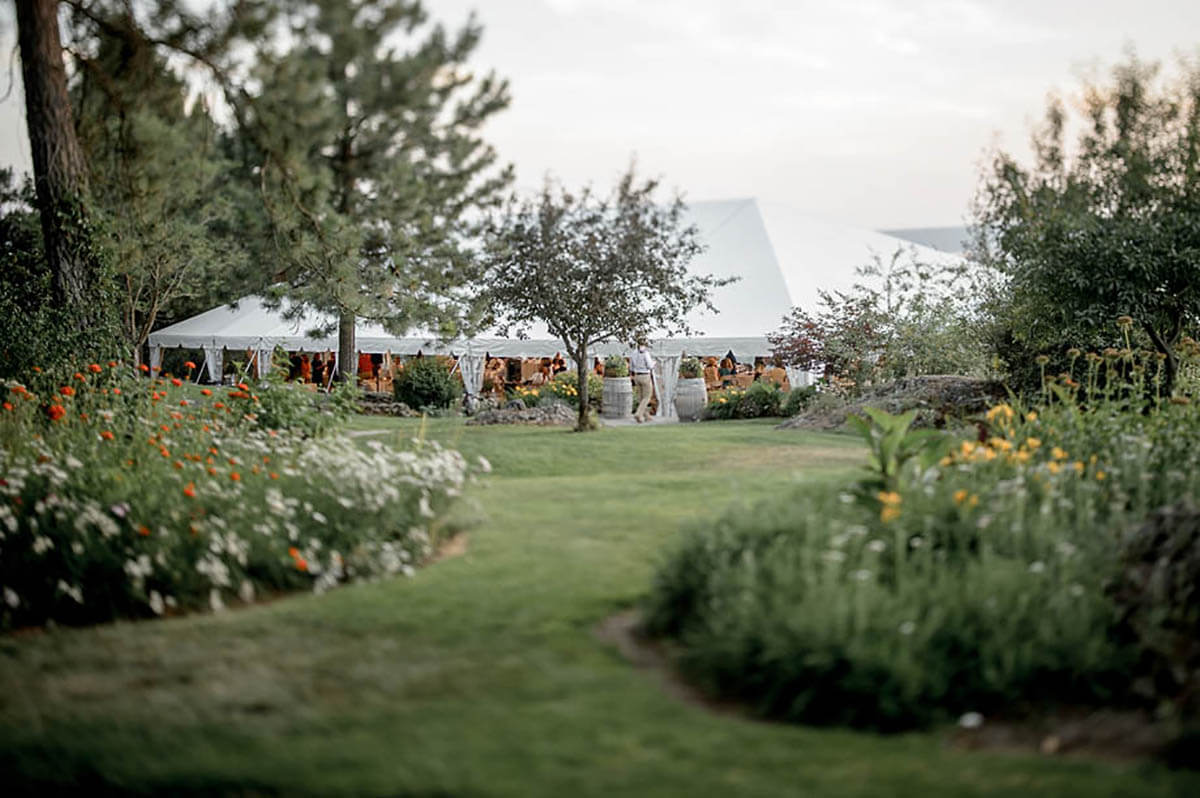 An exterior shot of the wedding tent and beautiful flowers and trees