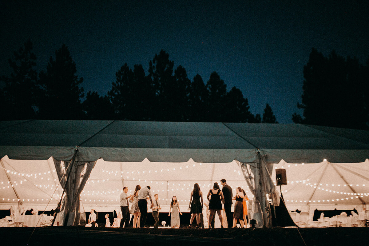 A night time shot of the wedding tent exterior with wedding party inside. Trees frame the photo against a night sky.