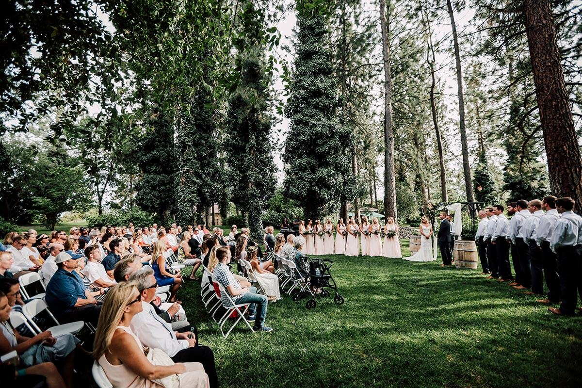 A photo of a wedding ceremony in the pine trees with crowd sitting to the left and the wedding party to the right