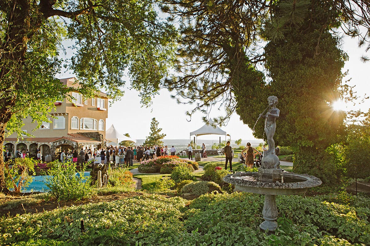 A sunlit photo of the Cliff House Estate and its surrounding courtyards. A crowd is gathered at the base of the Estate.