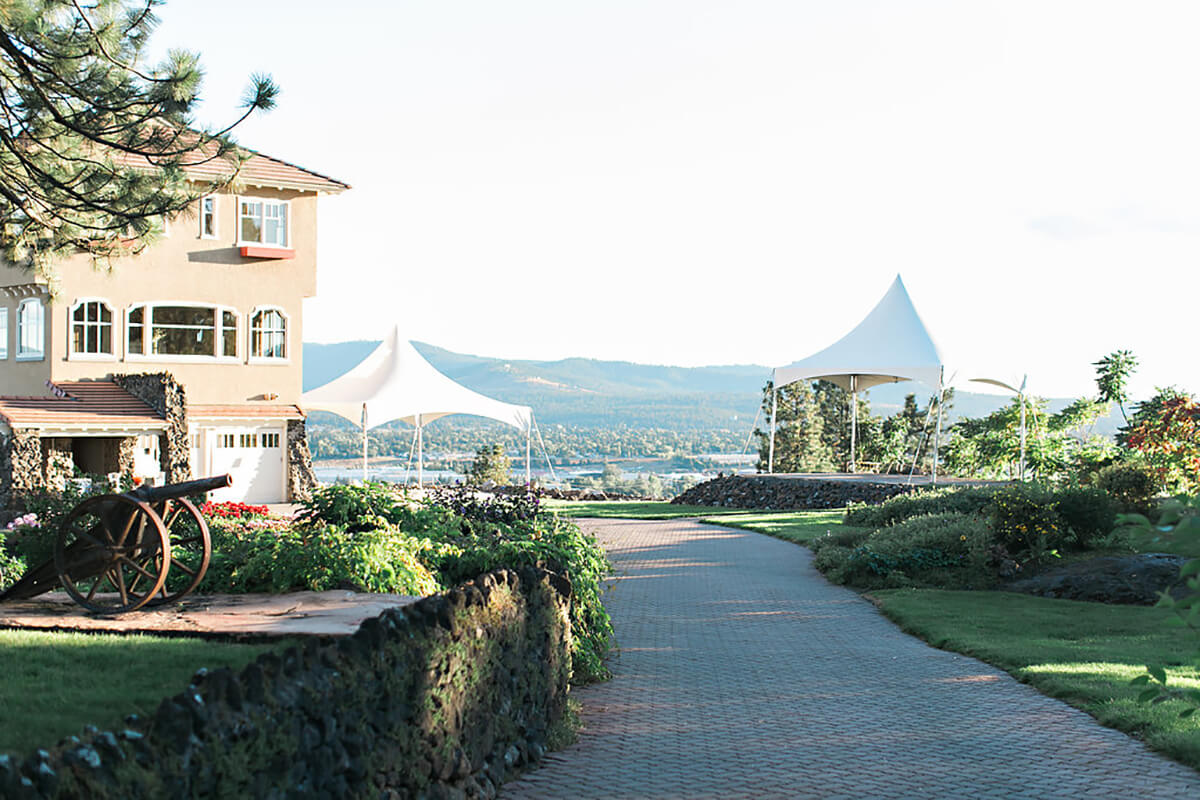 A photo of the path leading up the the Cliff House Estate. On the left is the Cliff House Estate and a cannon. Central is two tents and a scenic view.