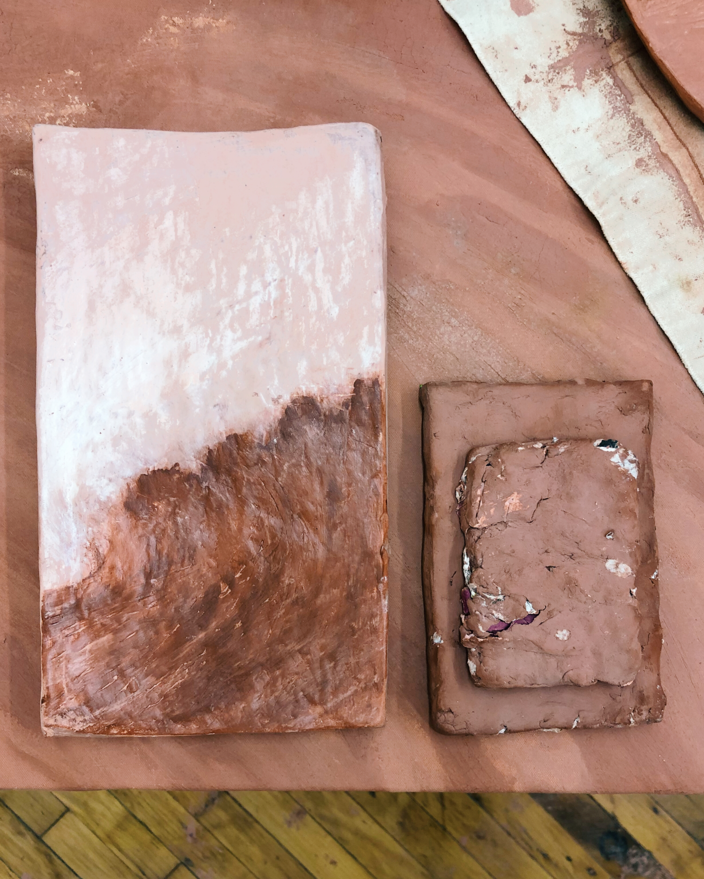 Clay tablets, painted, sculpted around torn book pages