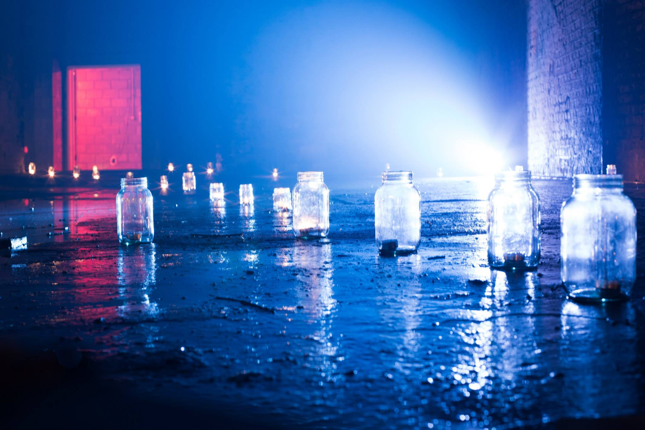 'He had set out candles as he had done the night before, and they glowed in jam jars around the floor...'