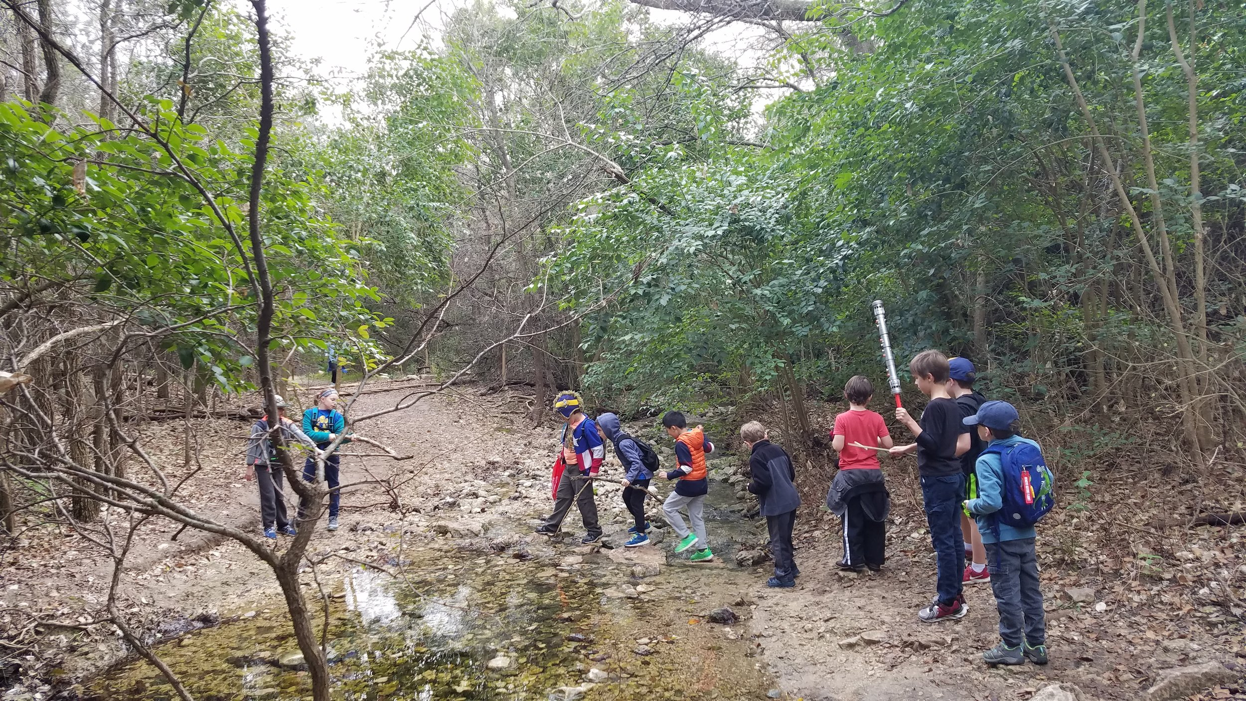 Cub Scouts enjoy crossing a small stream on Great Hills Trail.
