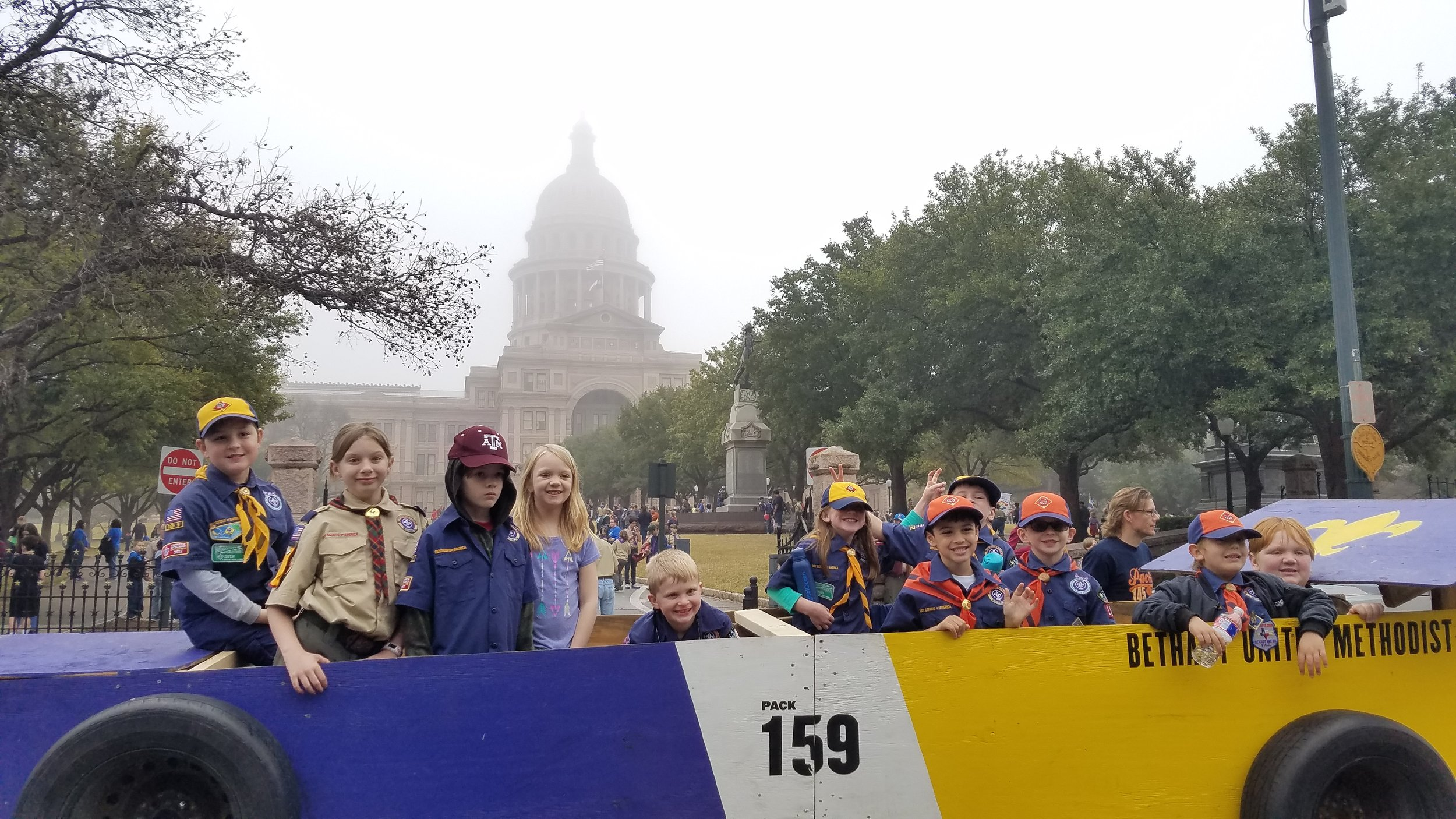 Cub scouts ride in the pack's Pinewood Derby car float for the misty 2019 Report to State Parade.