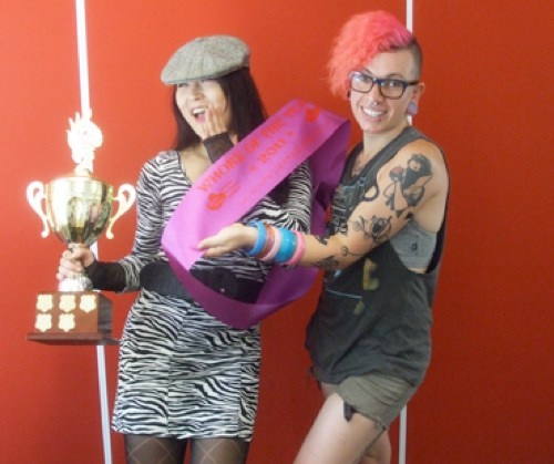 Jules Kim is presented with a trophy and a purple sash saying 'whore of the year'