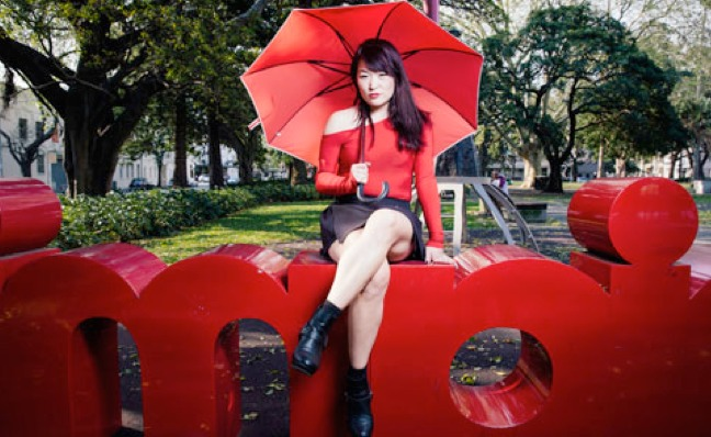 outdoor photo of Jules Kim with red umbrella