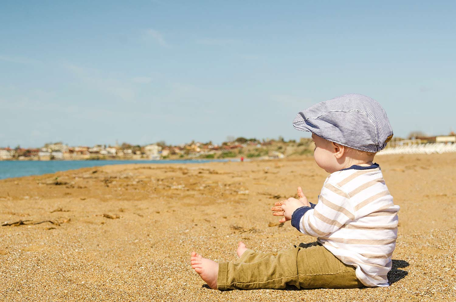 Little boy sitting on the beach, the Best Sunscreen For Kids: What To Look For And What Brands To Buy, featuring Dr. Alison Mitzner in the Huffington Post