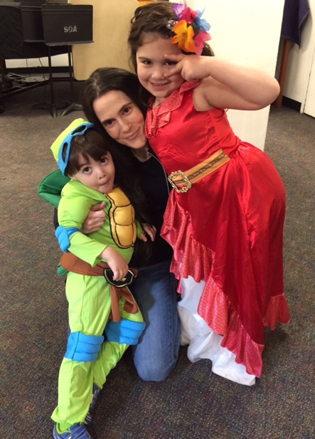 Dr. Alison Mitzner with her son and daughter, dressed up in costumes, offering parenting and wellness tips for moms