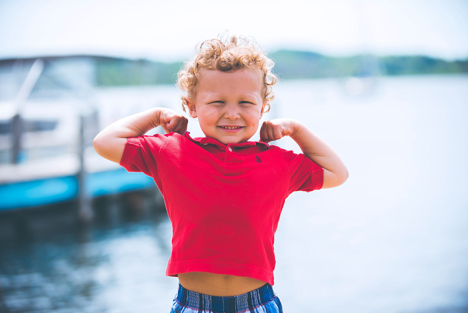 Little boy in red shirt flexing his muscles, 7 Little Wins to Boost Your Kid's Health, featuring Dr. Alison Mitzner in Parents Magazine