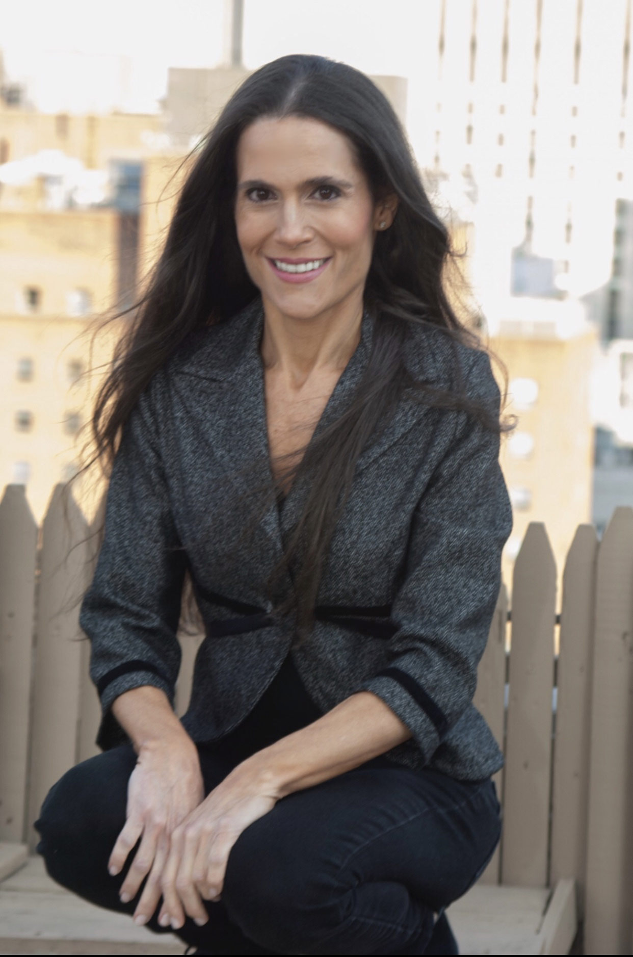 Dr. Alison Mitzner in gray suit on New York City rooftop, a board certified pediatrician and family wellness expert