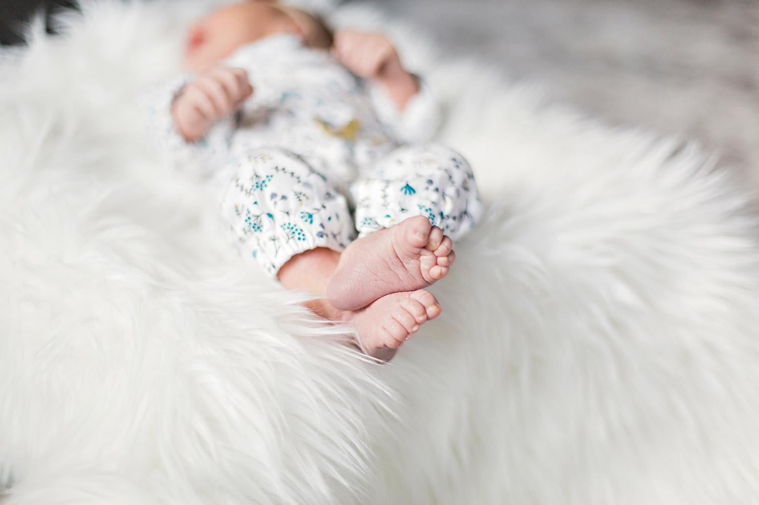 Newborn baby in floral onesie and white fluffy rug, what to know about newborn rashes