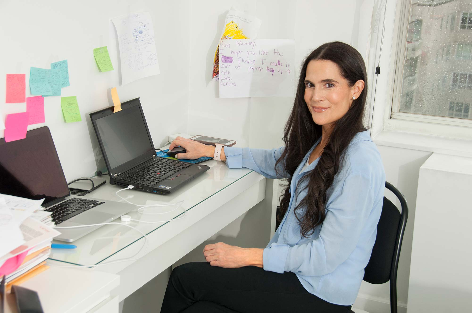 Dr. Alison Mitzner working at her desk on her laptop in a blue shirt, becoming a mom expert source for parents