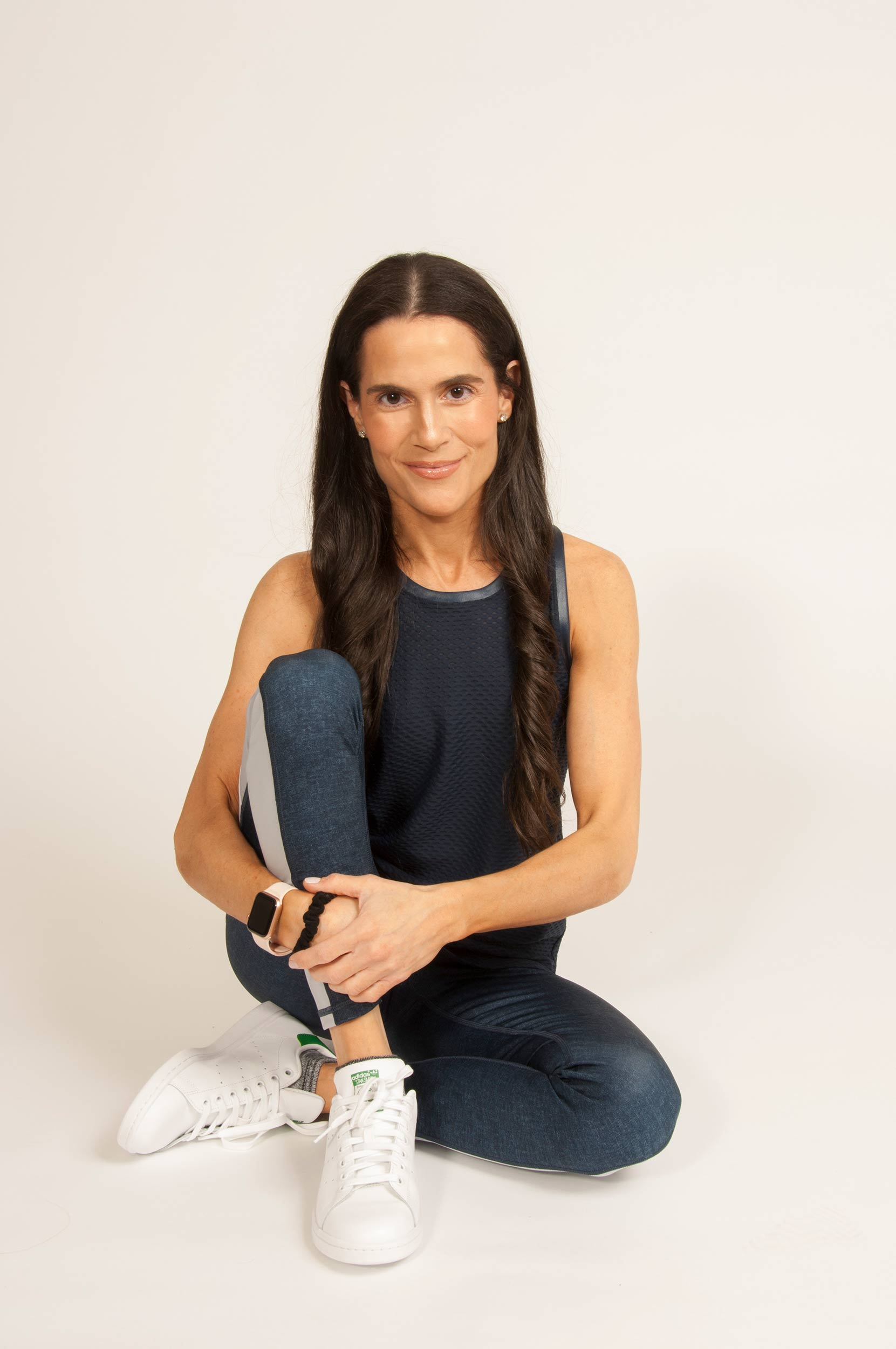 Dr. Alison Mitzner in a navy blue workout outfit and white tennis shoes, fitness guru, mom expert, postpartum wellness tips