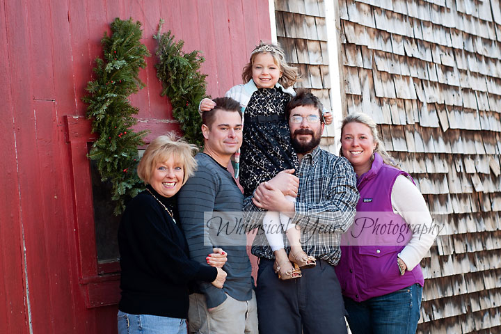 family portrait against a barn with red door at christmas time