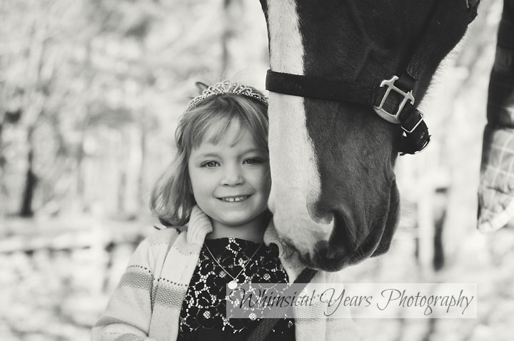 black and white photo of little girl standing close to her horse