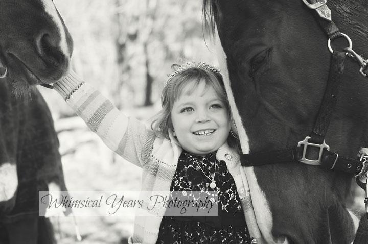 little girl standing between two big horses