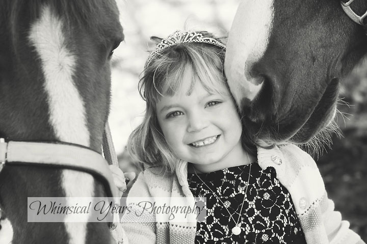 horse nuzzling the cheek of a little girl