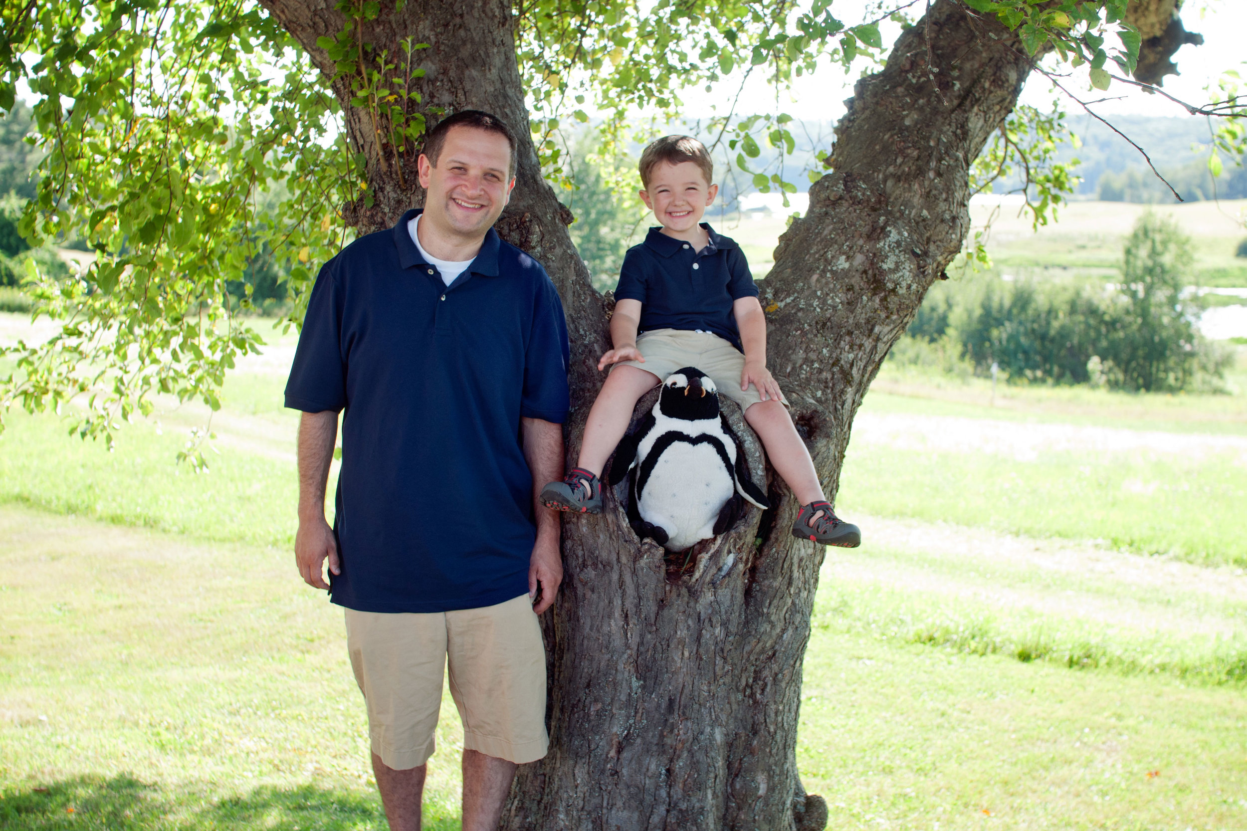 little boy sitting in the nook of a tree smiling with his uncle by his side