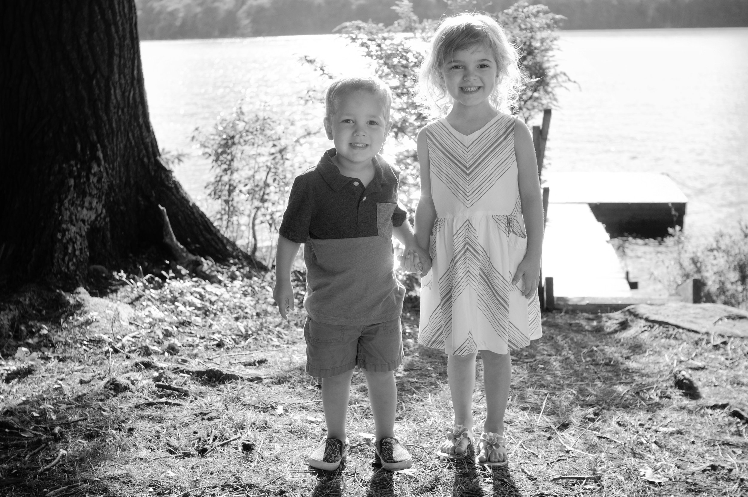 black and white photo of little boy and girl holding hands by a lake