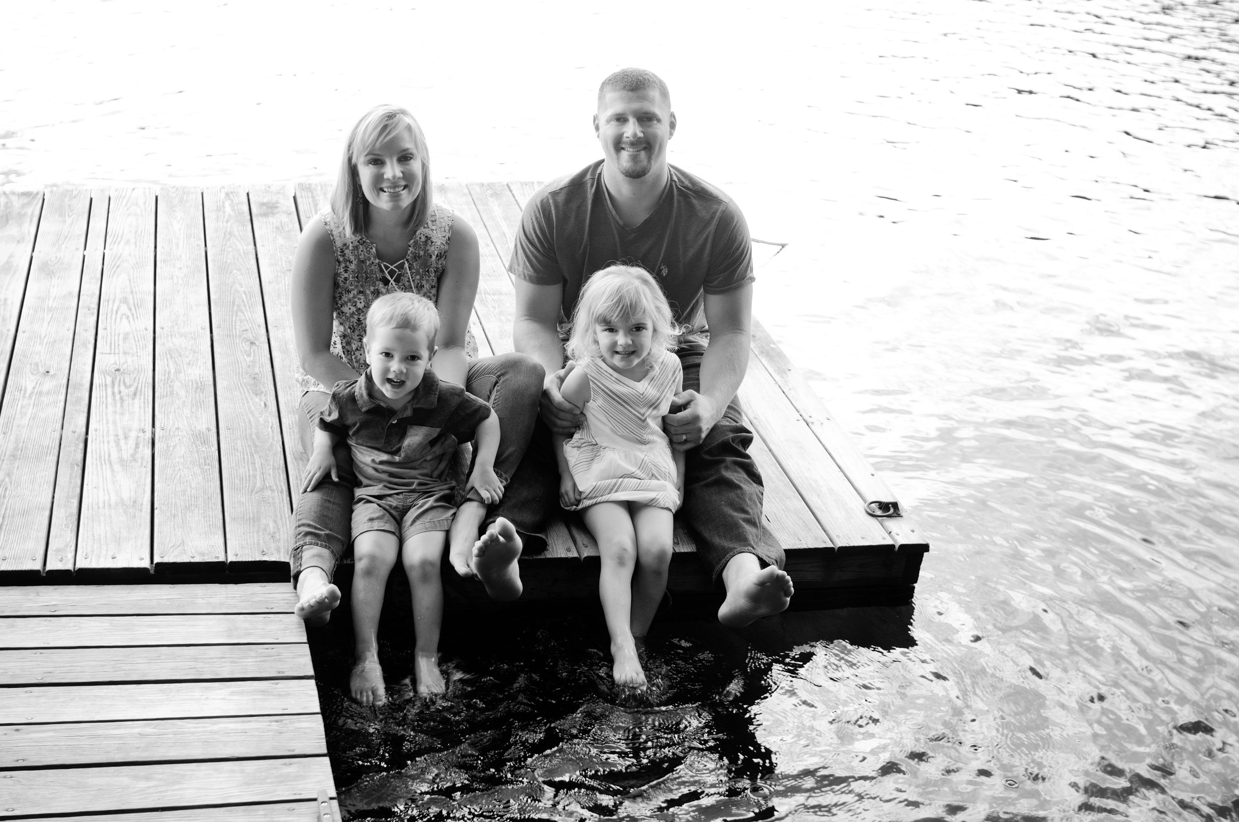 Family of four sitting on dock at lake
