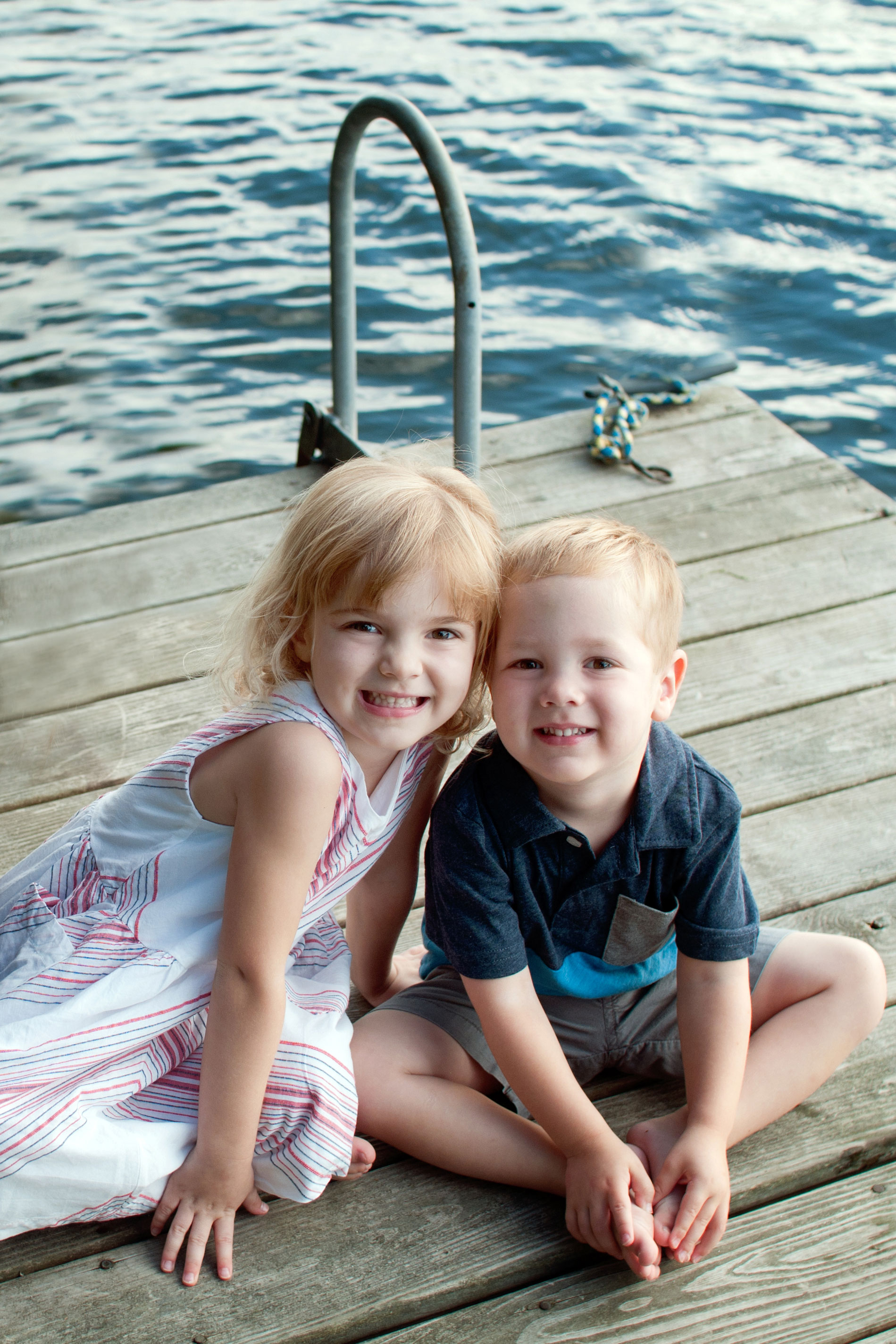 young girl and boy sitting together smiling on a dock