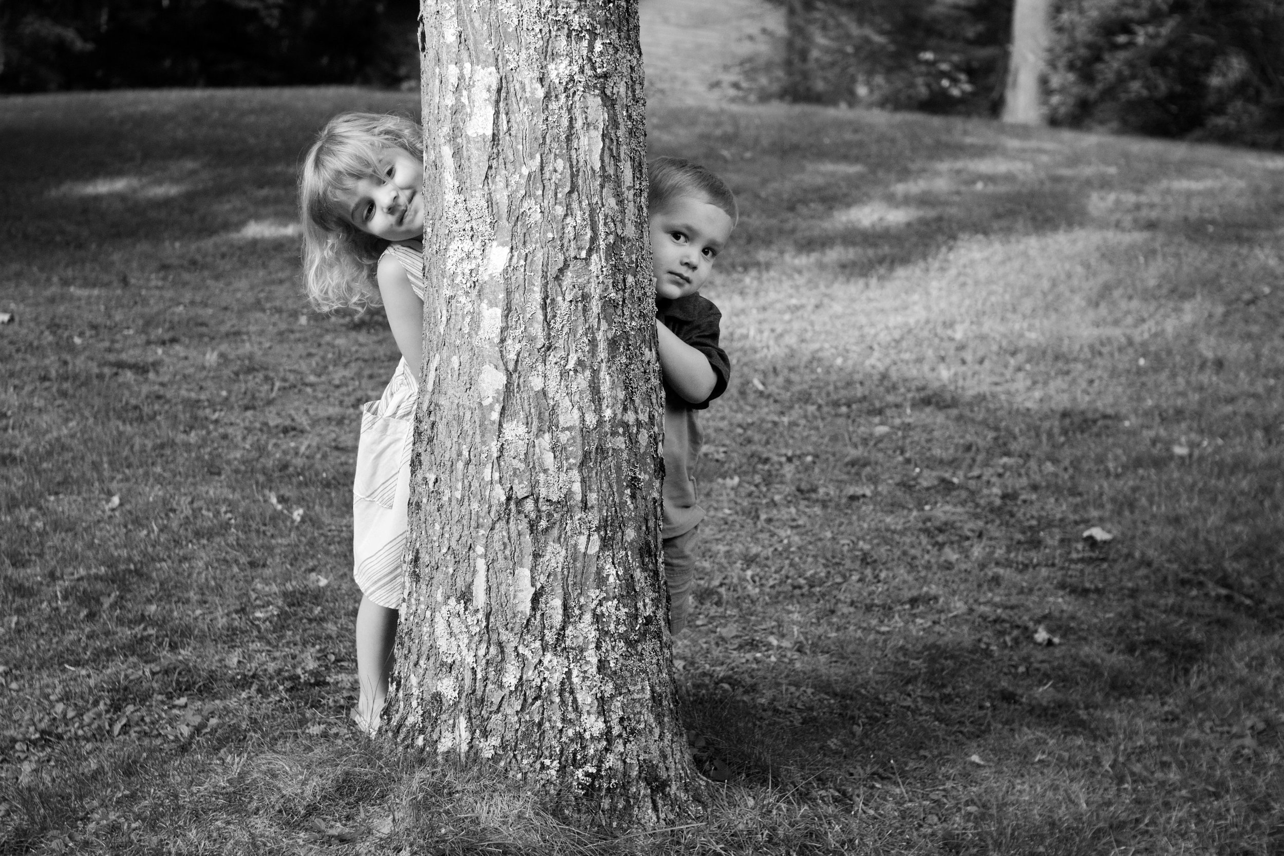 black and white photo of little boy and girl peeking from behind a tree