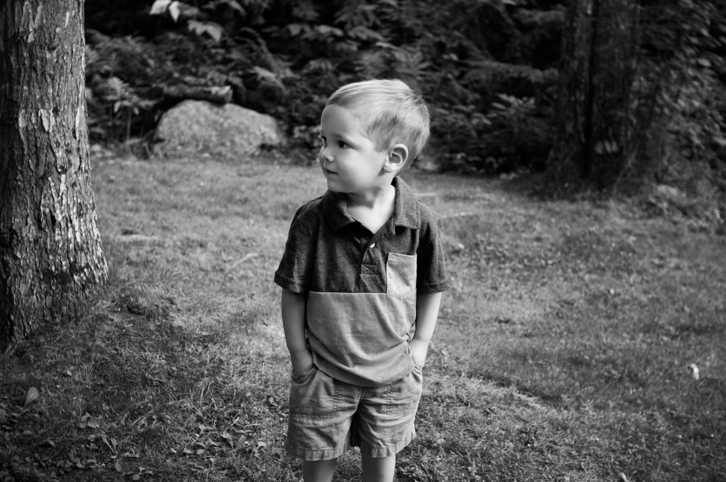 little boy standing in grass with hands in his pockets