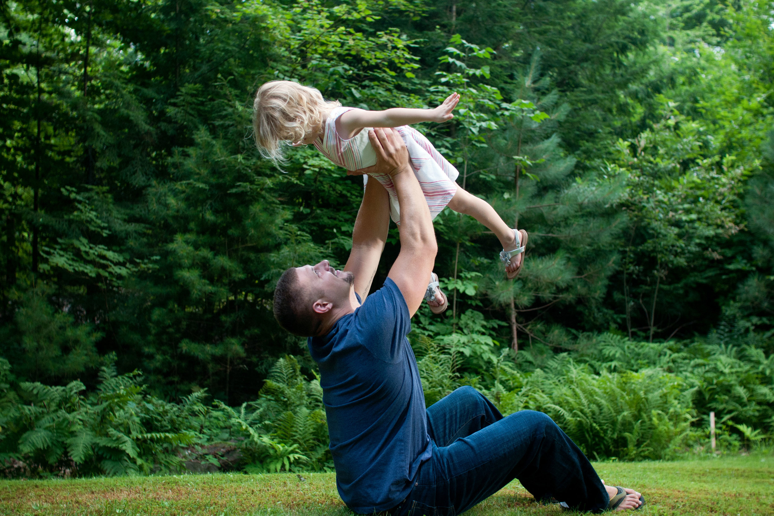 Father lifting his young daughter into the air