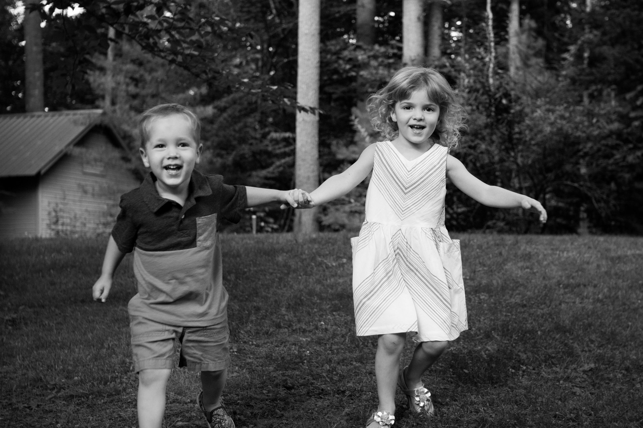 black and white photo of little boy and girl holding hands running