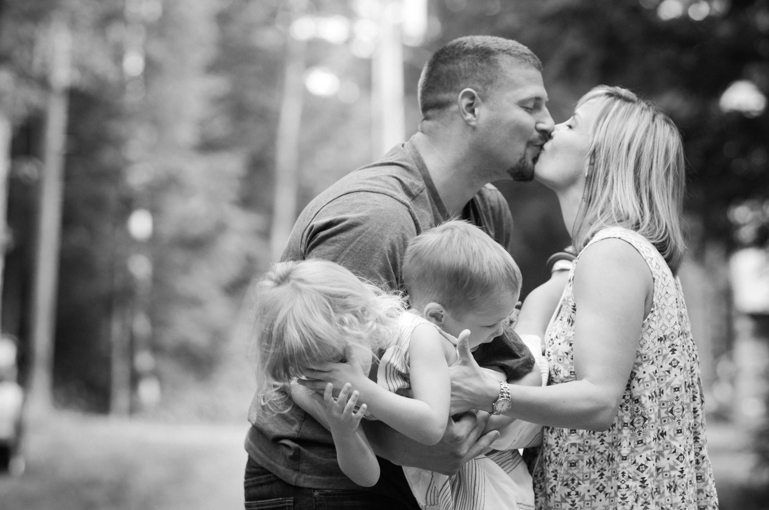 black and white silly candid portrait of young family
