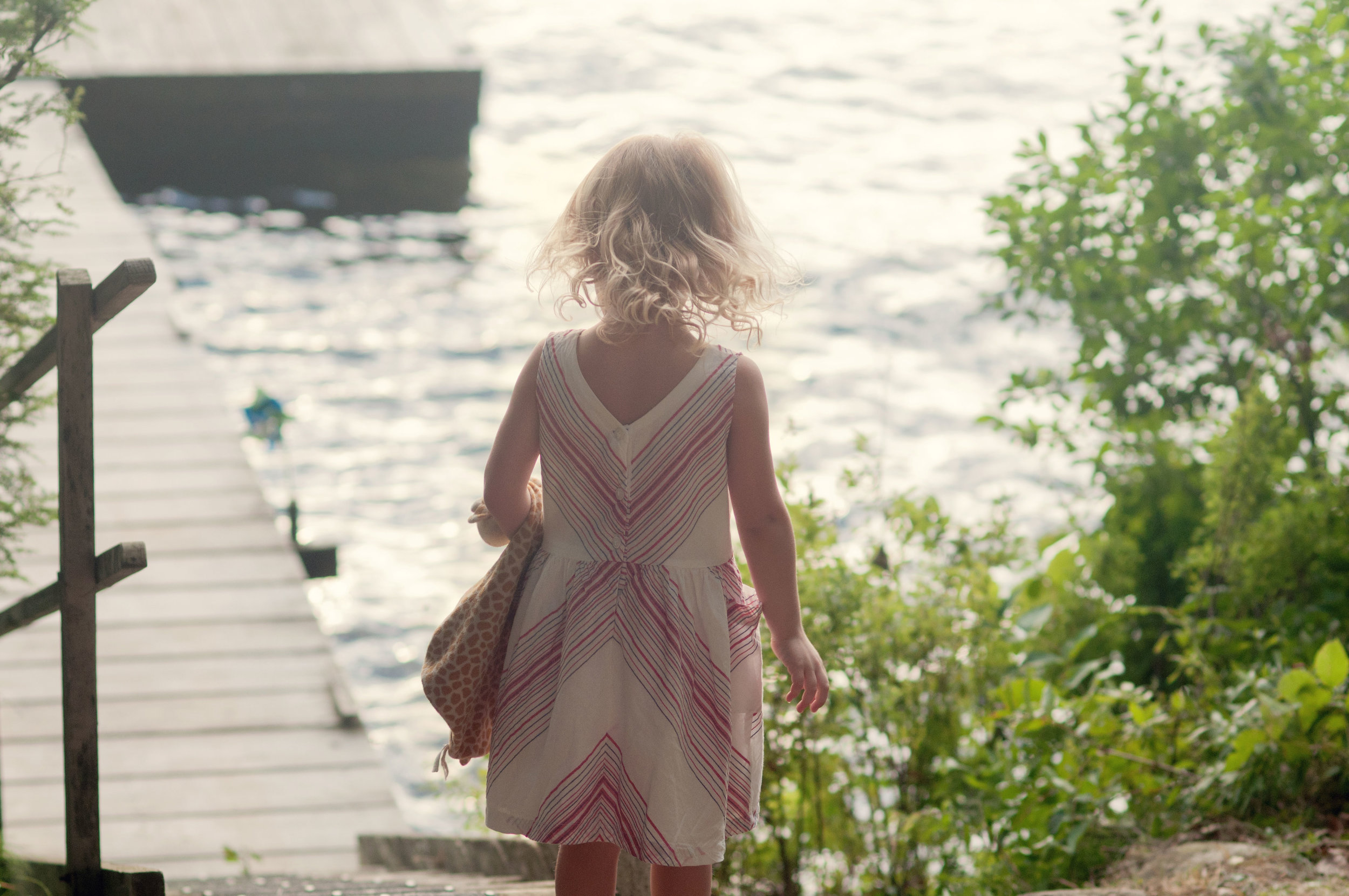 little girl walking to a dock at a lake
