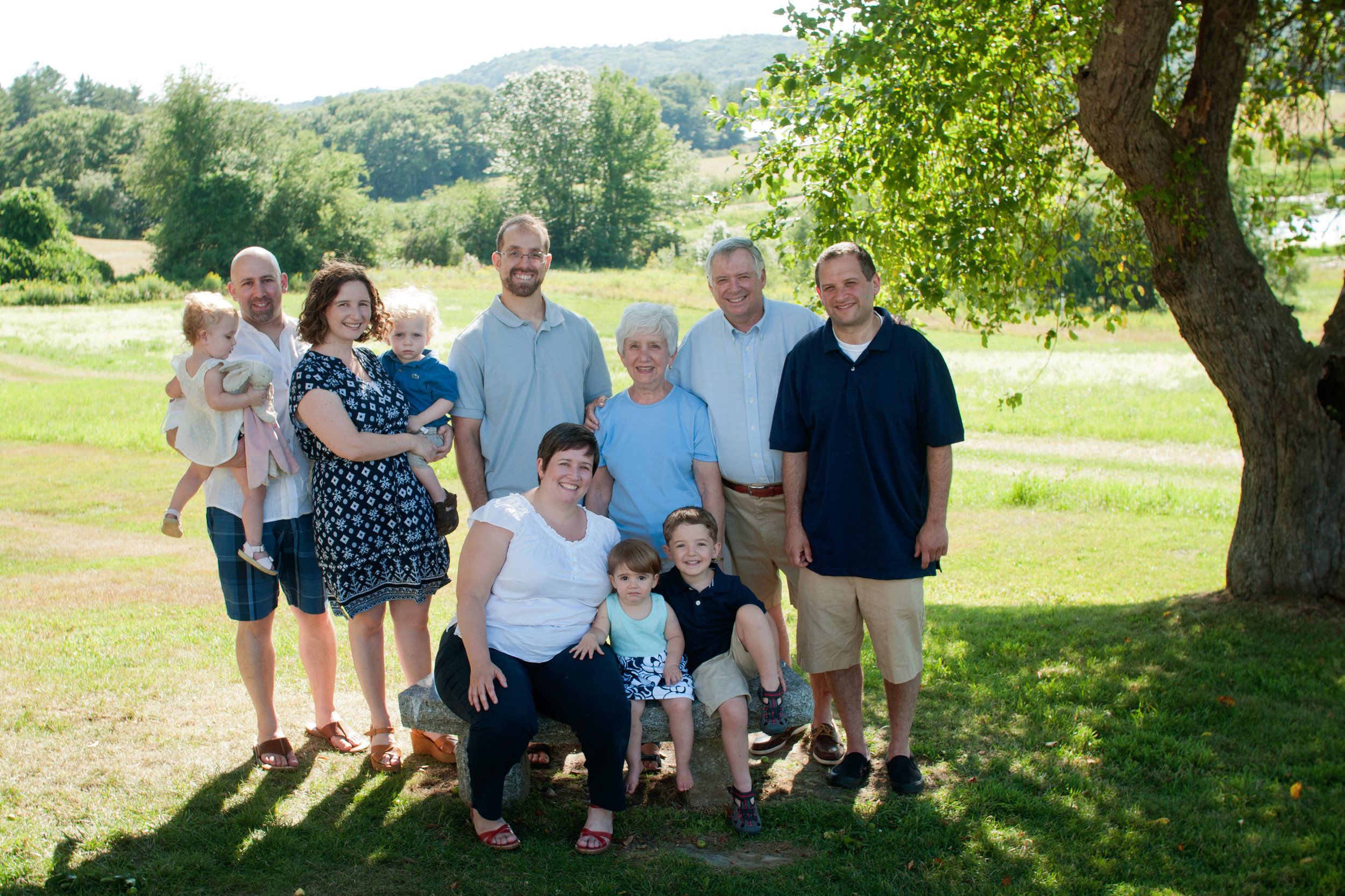 portrait of eleven people in the shade of a large field