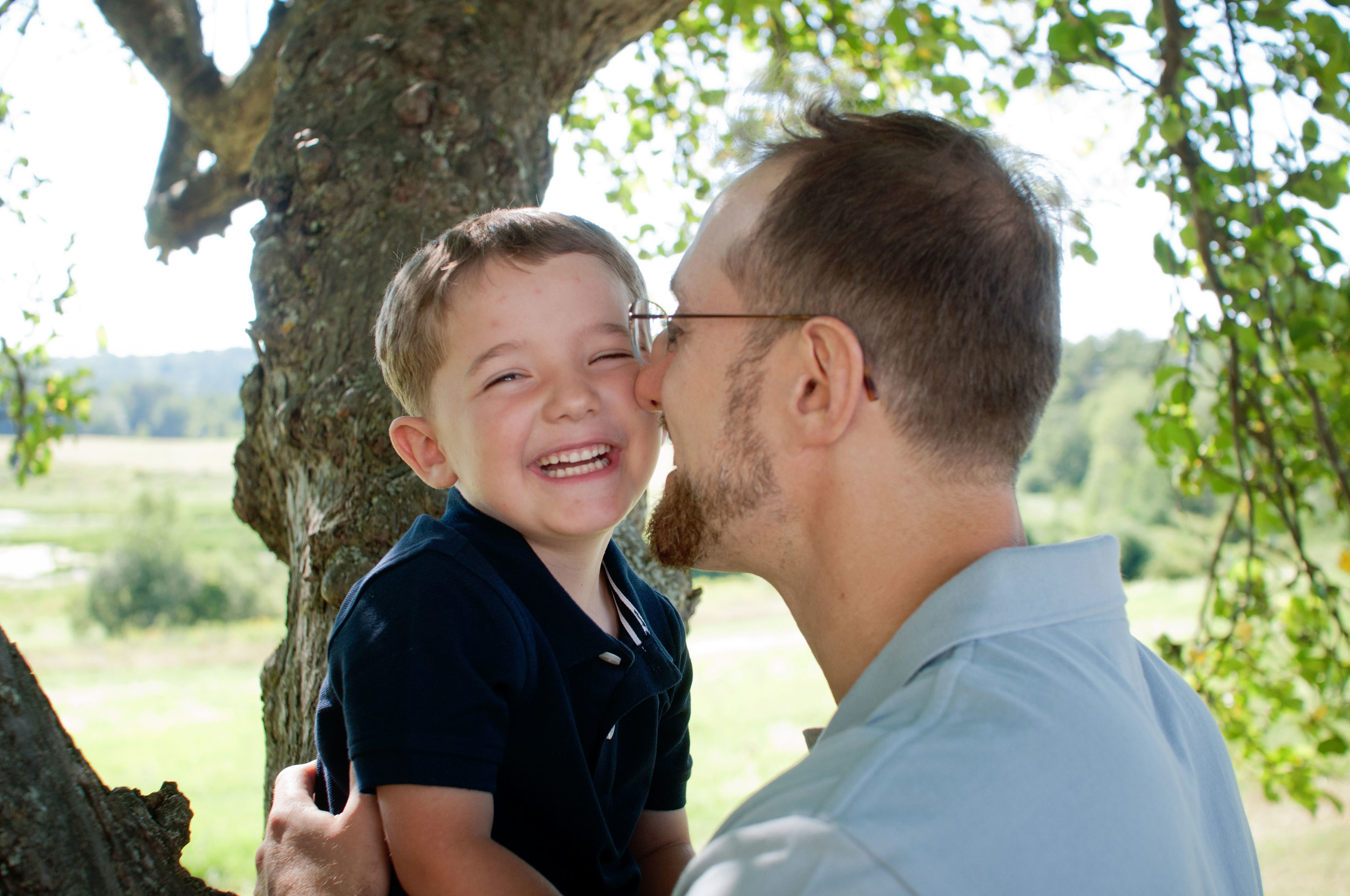 silly photo of young boy and his father giggling together in a shady tree