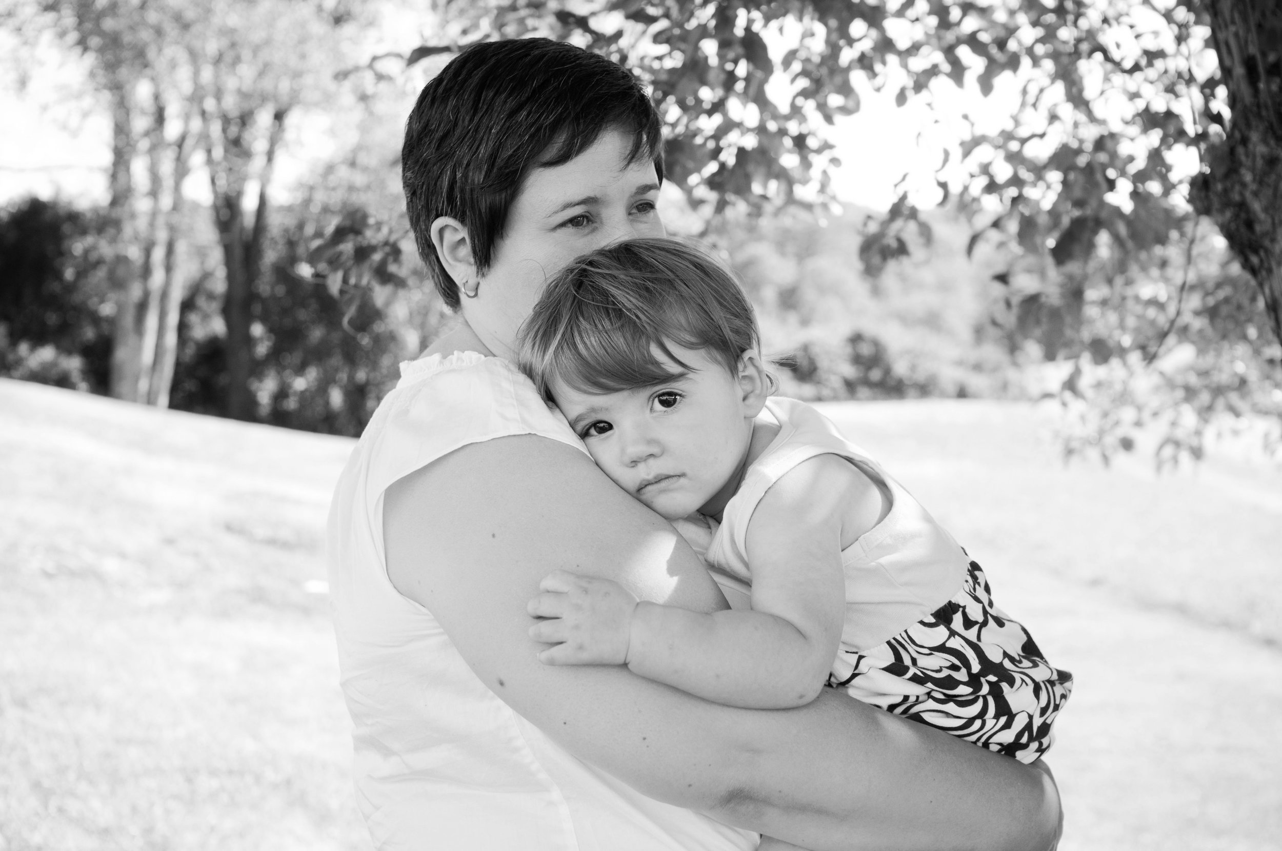black and white photo of little girl resting in her mothers arms