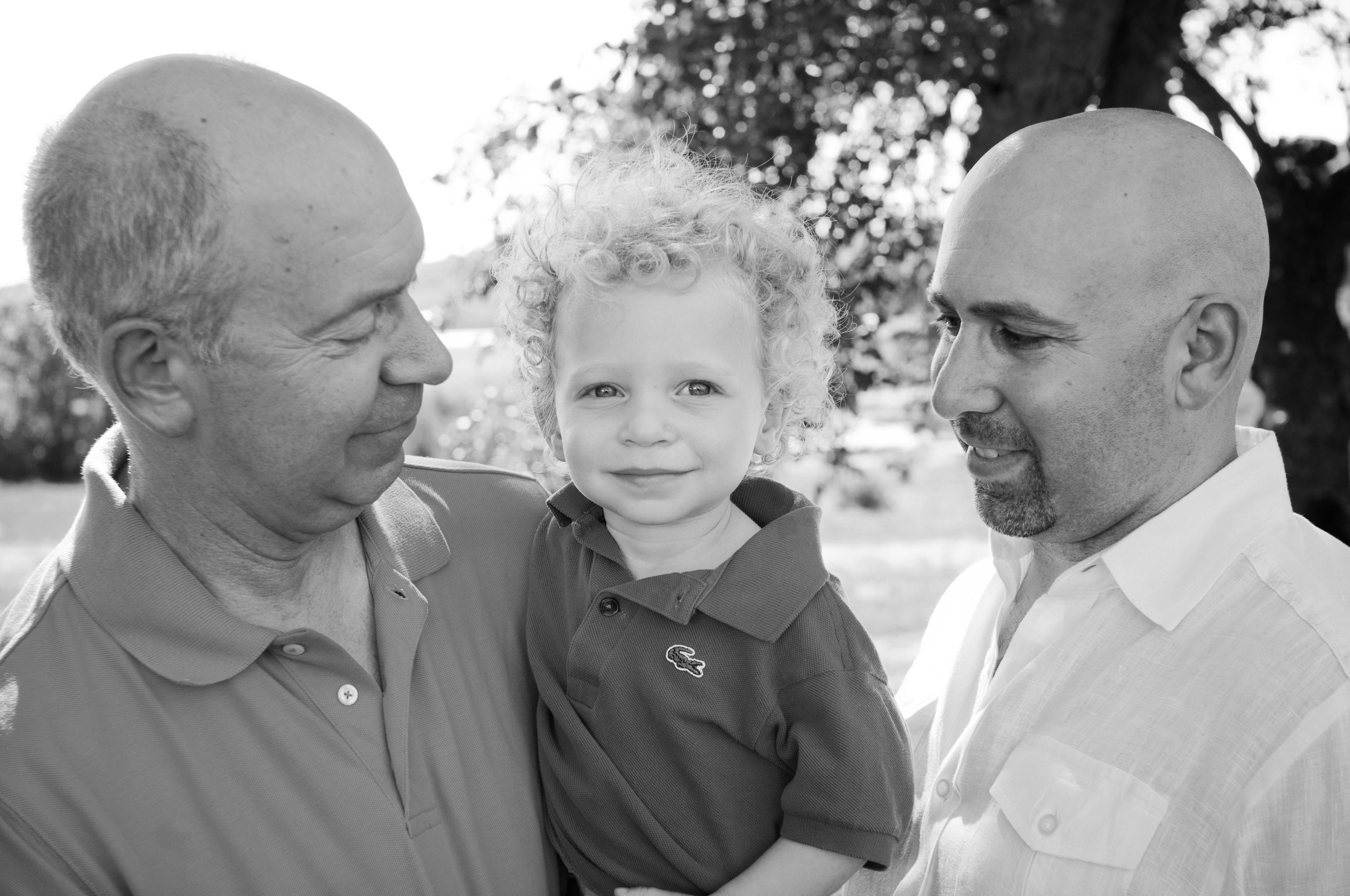 black and white photo of grandfather and adult son holding grandson