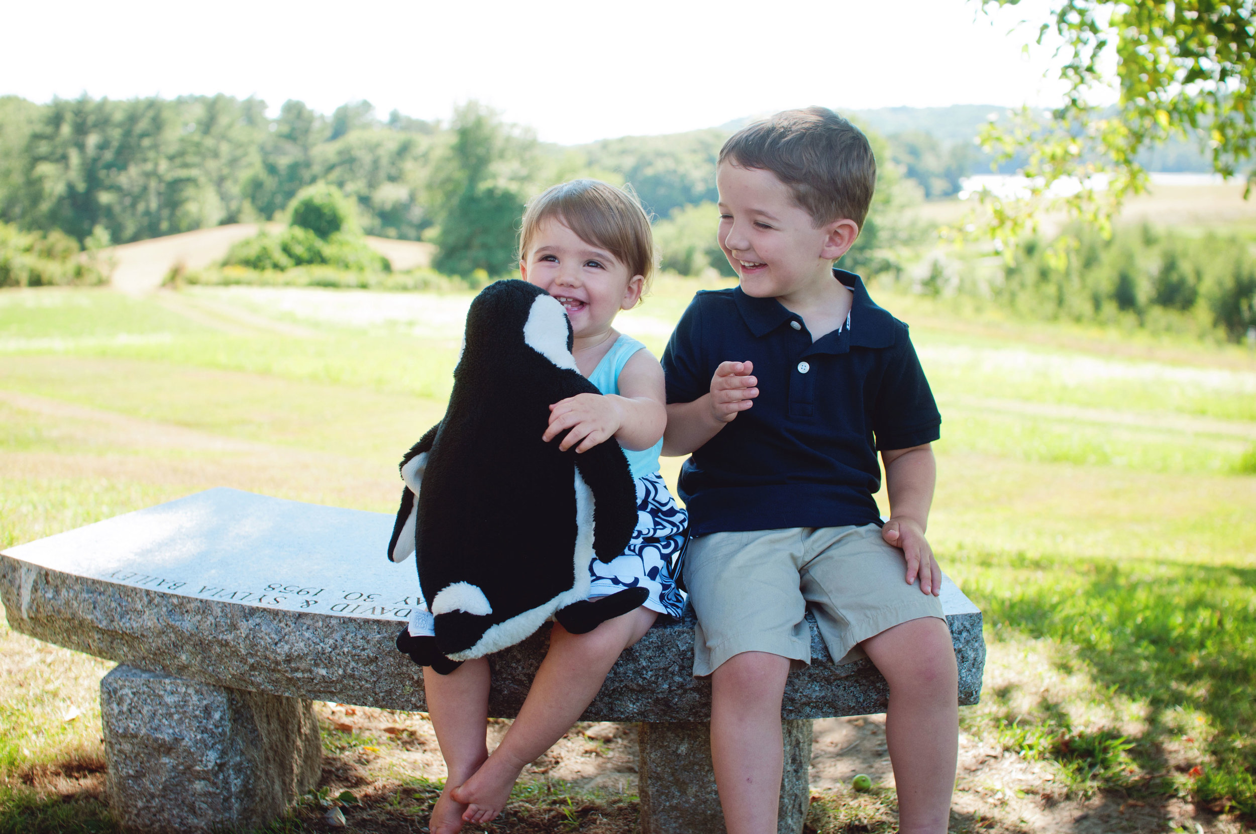 two young children sitting on bench laughing