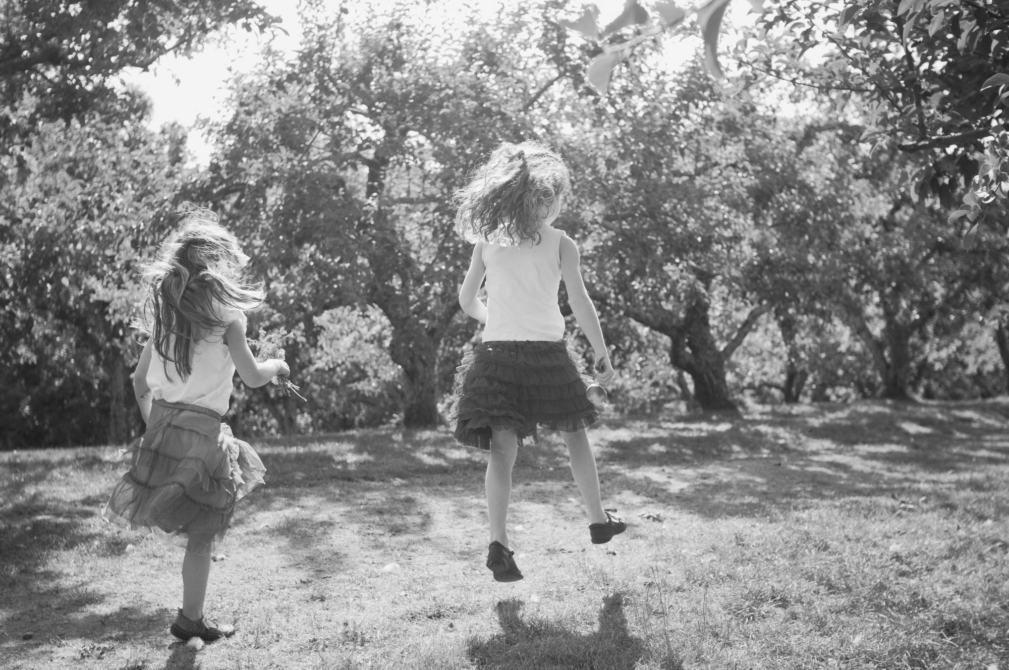 black and white photo of two sisters skipping through apple orchard