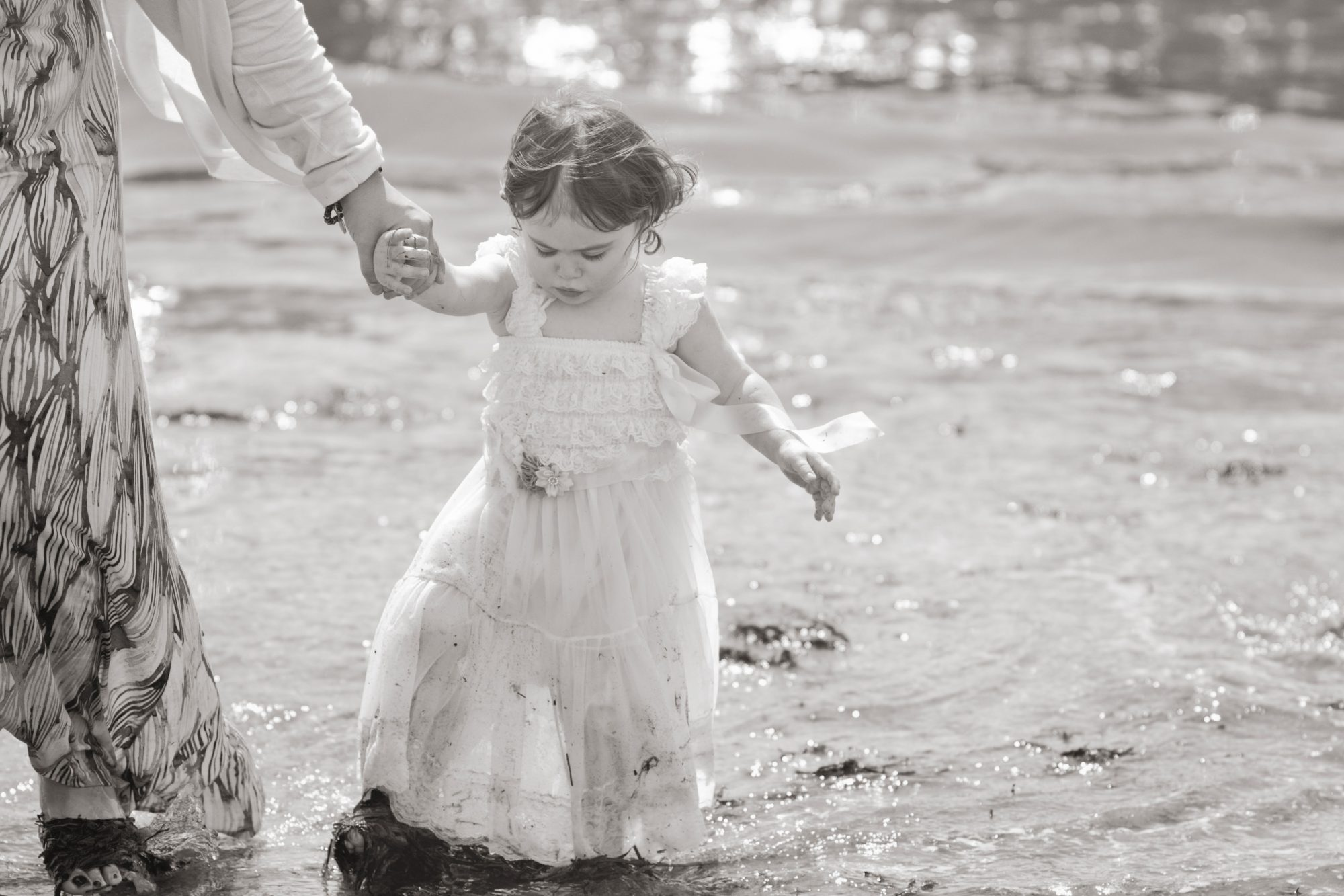 black and white photo of little girl on beach