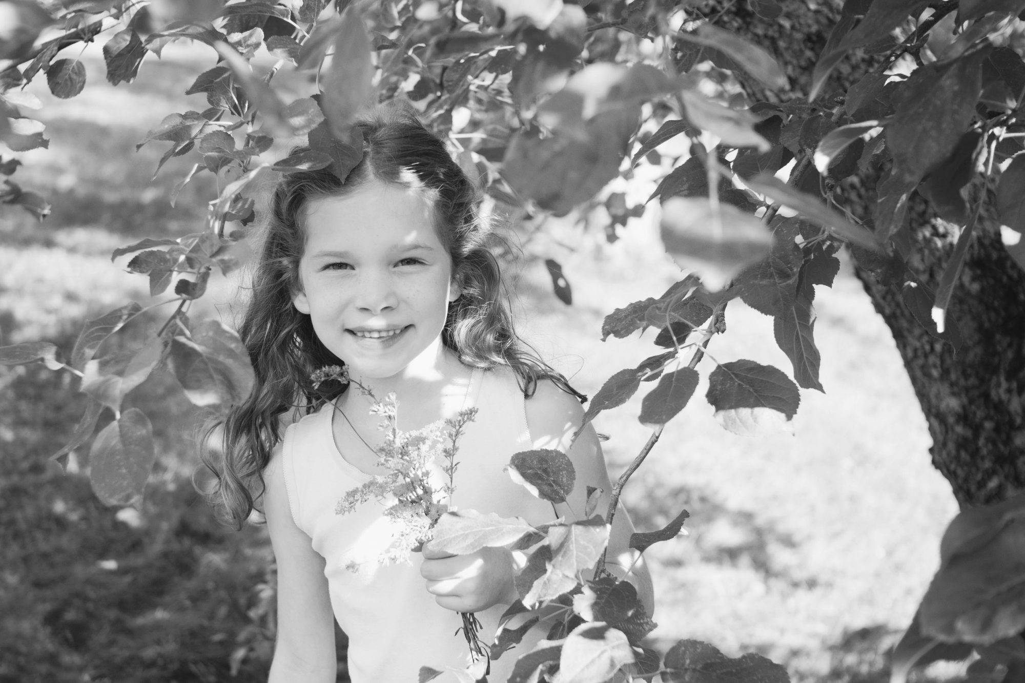 Black and white portrait of young girl next to apple tree